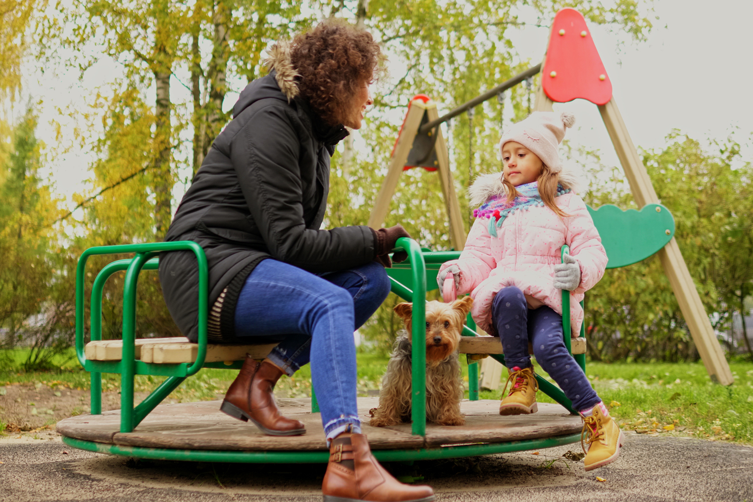 Mother with daughter riding carousel on a playground.